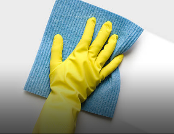 Gloved hand wiping away stick substances from hard surface or counter